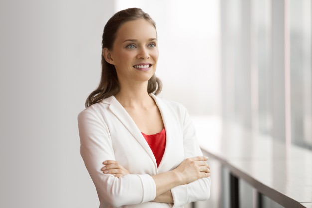pretty-smiling-business-woman-standing-at-window_1262-1069
